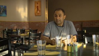 Restaurant owner sits at a table.