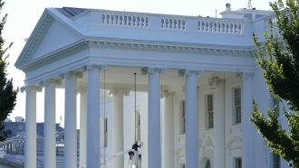 A worker works on the light fixture over the North Portico of the White House in Washington, D.C.