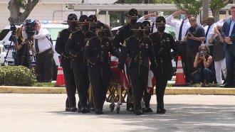 Officers carry a casket.