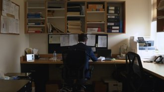 Lawyer sits at a desk.
