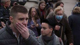 Students react as they gather outside the Perm State University in Perm.