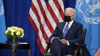 President Joe Biden sits before U.N. flag