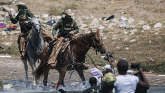 U.S. Border Patrol agents attempt to contain migrants as they cross the Rio Grande from Mexico into Texas.