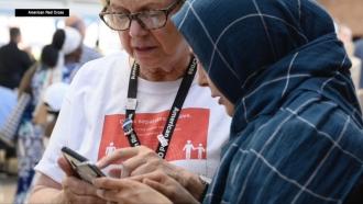 Red Cross volunteer helps woman.
