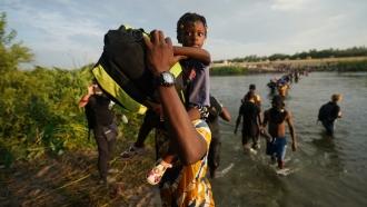 Migrants, many from Haiti, cross the Rio Grande from Del Rio, Texas, to return to Ciudad Acuna, Mexico