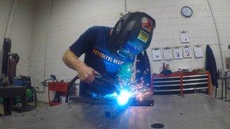 Man welds bars together.