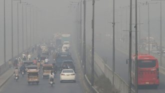 vehicles drive on a highway as smog envelops the area of Lahore, Pakistan