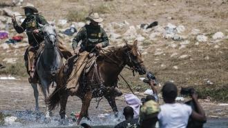U.S. Border Patrol officers on horseback confront migrants