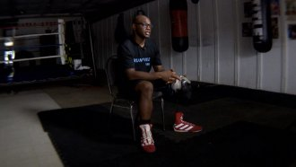 A boxer sits outside the ring.