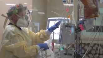 Nurse touches a machine.