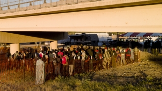 Migrants, many from Haiti, wait in lines to board buses under the Del Rio International Bridge