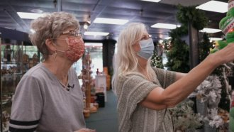 Two women look at a holiday store display.