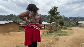 A woman stands hear her home in Beni, eastern Congo.