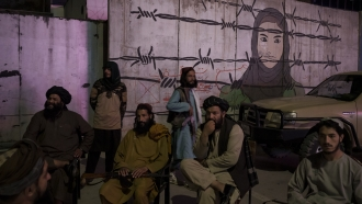 Taliban members sit in front of a mural depicting a woman behind barbed wire