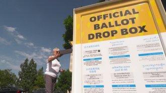 Woman drops an envelope into a ballot box.