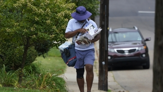 A U.S. Postal Service carrier walks his route to deliver the mail