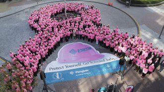 Hundreds of New Yorkers wearing pink hard hats and pink shirts form a pink ribbon in honor of Breast Cancer Awareness Month