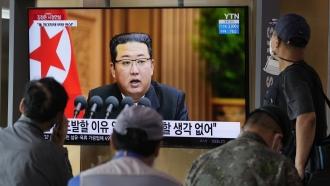 People watch a TV screen showing North Korean leader Kim Jong Un.