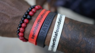 A man wears bracelets with the name of his mental health foundation on them