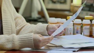 A woman looks at bills