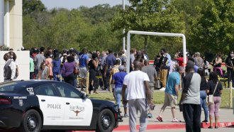 Families stand outside waiting to be reunited with their children after a school shooting