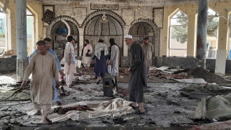 People view the damage inside of a mosque following a bombing in Kunduz province in northern Afghanistan.