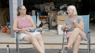 Two women sit and talk