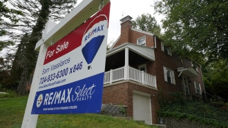 """A """"for sale"""" sign is displayed outside a home"""