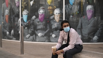 A man takes a coffee break in front of a COVID 19-themed mural, in Beverly Hills, California.
