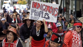 A woman holds a sign for Indigenous Peoples Day during a demonstration and march