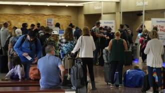 Passengers queue up at the ticketing counter for Southwest Airlines flights