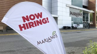 A sign in the parking lot of Mariano's grocery store advertises the availability of jobs