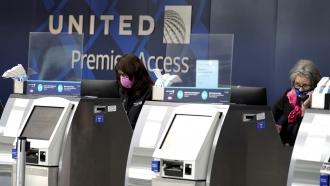 United Airlines employees work at ticket counters.