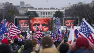 In this Jan 6. 2021, file photo, the face of President Donald Trump appears on large screens.