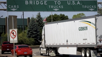 """""""Bridge to U.S.A."""" sign over highway as cars cross into the U.S. from Canada"""