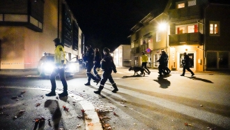 Police walk at the scene after an attack in Kongsberg, Norway.