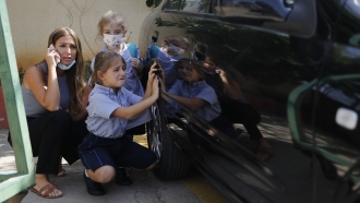 A Lebanese mother with her children hide behind a car from sniper fire outside a school in Beirut, Lebanon.