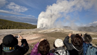 Tourists photograph Old Faithful geyser in Yellowstone National Park, Wyoming.