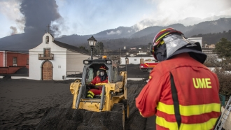 Military Emergency Unit personal clear black ash from a volcano as it erupts on the Canary island of La Palma, Spain.