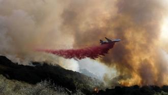 An air tanker drops retardant on a wildfire