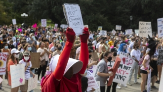 In this Oct. 2, 2021 image, a woman attends the Women's March ATX rally, at the Texas State Capitol in Austin, Texas.