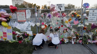 People light candles at a makeshift memorial outside Marjory Stoneman Douglas High School in 2018