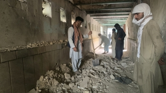 People inspect the inside of a mosque following a suicide bomber's attack in the city of Kandahar, southwest Afghanistan.