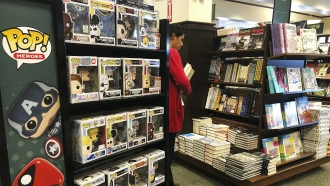 A woman stocks shelves with books at a Barnes and Noble bookstore