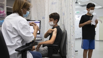 In this June 6, 2021 file photo, a youth receives a Pfizer-BioNTech COVID-19 vaccine in Israel.