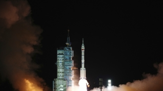 A photo released by Xinhua News Agency shows the crewed spaceship Shenzhou-13, atop a Long March-2F carrier rocket.