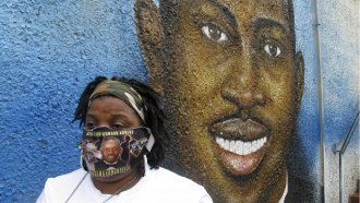 A woman stands in front of a mural of her slain nephew, Ahmaud Arbery
