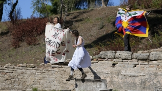 """Protesters displaying a Tibetan flag and a banner reading """"No genocide games"""""""