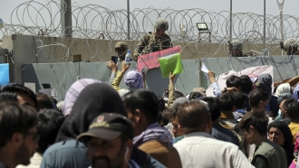 A U.S. soldier holds a sign indicating a gate is closed as hundreds of people gather at the Airport in Kabul, Afghanistan.