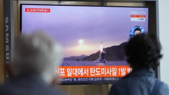 People watch a TV screen showing a news program reporting about North Korea's missile launch.